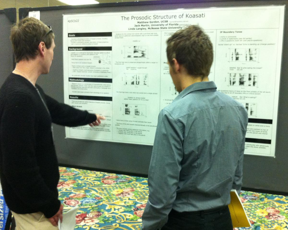 Professor Matthew Gordon and graduate student Joseph Brooks discussing a poster at a conference.